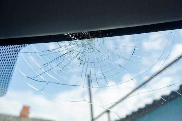 Zepsuta szyba z dużą ilością pęknięć i drobnych kawałków szkła, uszkodzony samochód