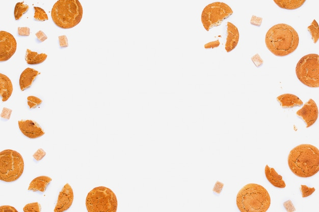 Zepsute ciasteczka i kostki cukru trzcinowego na białym, copyspace, układ płaskiej ramy