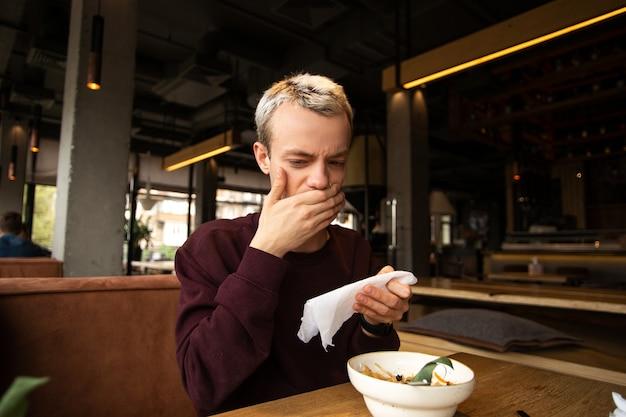 Zepsute jedzenie w restauracji. niezadowolony młody człowiek w kawiarni zakrywa usta dłonią zniesmaczoną smakiem jedzenia
