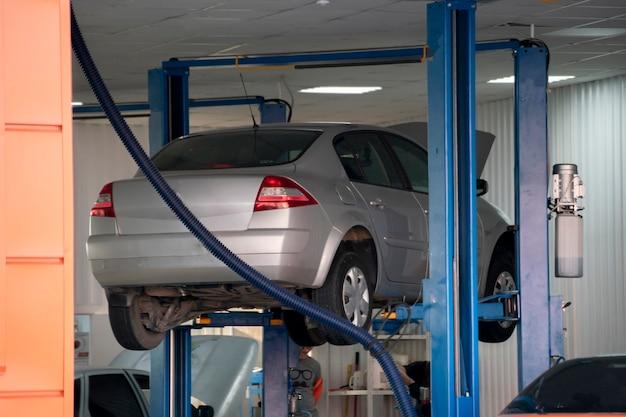 Zepsute samochody na podnośniku hydraulicznym czekające na wymianę części