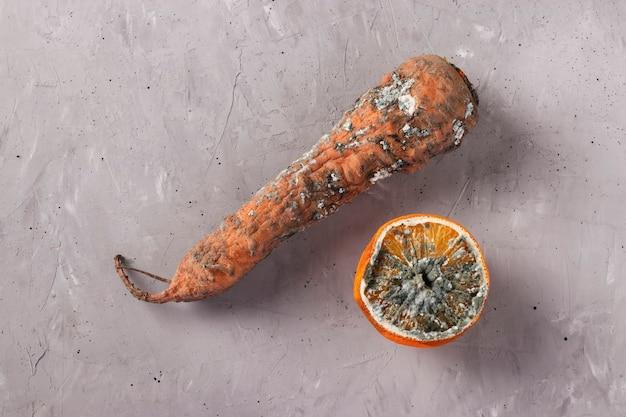 Zepsute zgniłe potrawy pleśnią: marchew i pół pomarańczy na szarym tle, zbliżenie, widok z góry