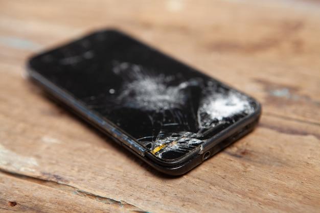 Zepsuty ekran smartfona na drewnianej powierzchni