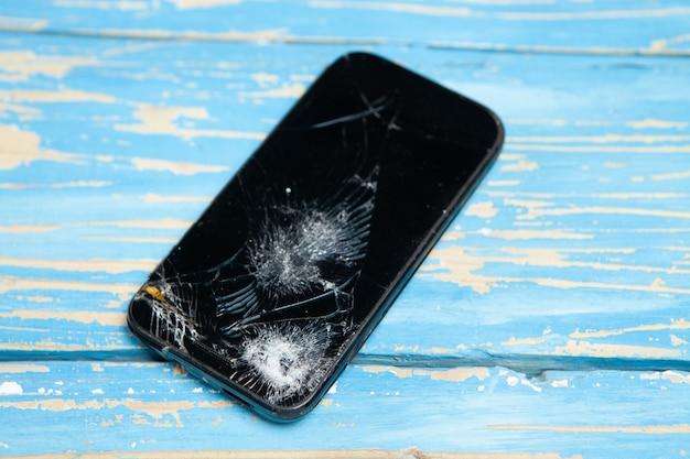 Zepsuty ekran smartfona na drewnianym tle