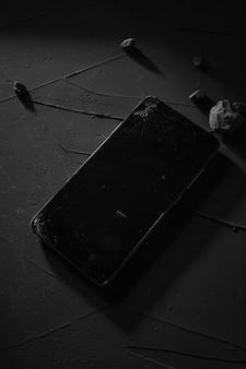 Zepsuty ekran telefonu na betonowym stole z twardym światłem, cieniami