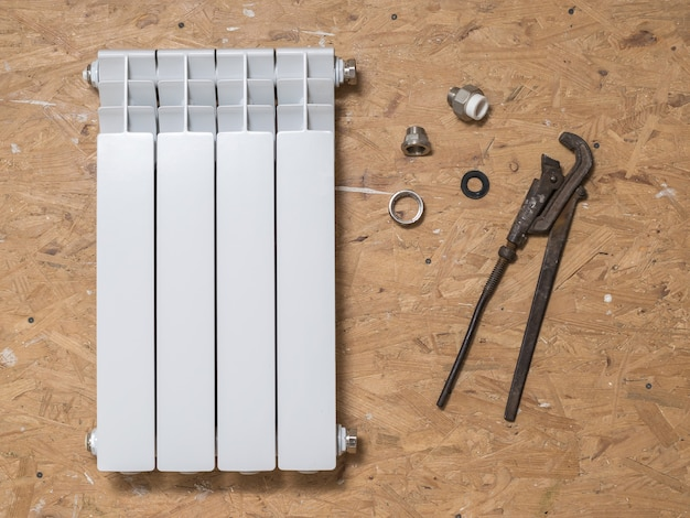 Zepsuty grzejnik i narzędzia do naprawy na drewnianej podłodze. wypadek systemu ogrzewania prywatnego domu. grzejnik grzewczy.