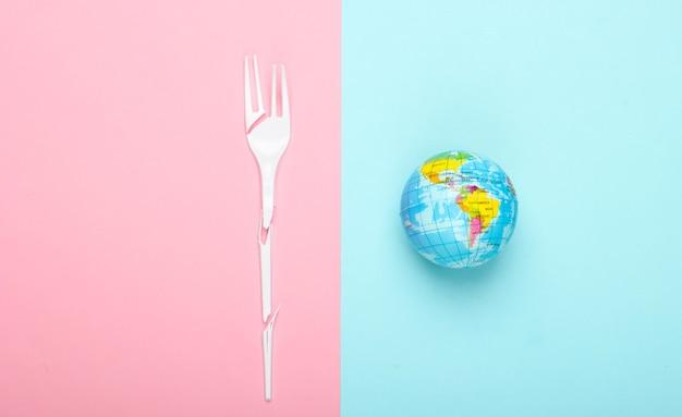 Zepsuty plastikowy widelec i światowa kula ziemska