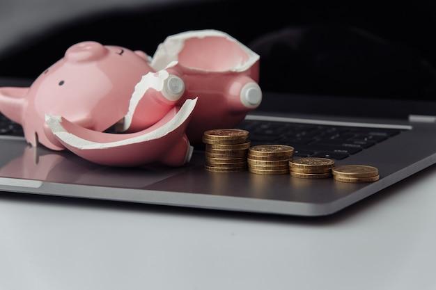 Zepsuty skarbonka i stos monet na klawiaturze