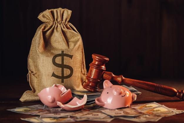 Zepsuty skarbonka z workiem pieniędzy i młotkiem sędziego. pojęcie gospodarki.