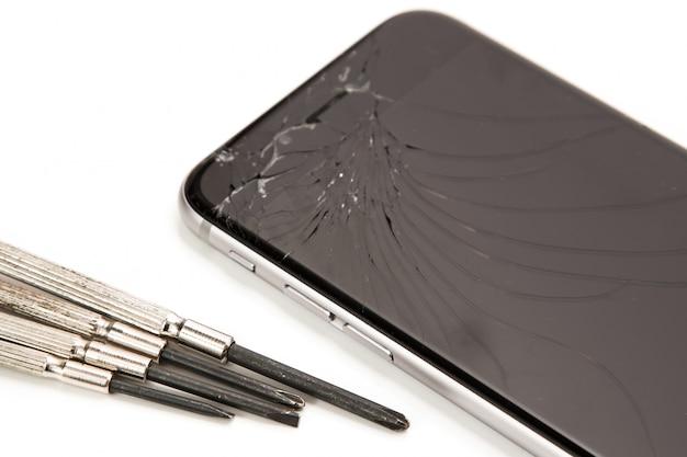 Zepsuty smartfon i małe śrubokręty do naprawy