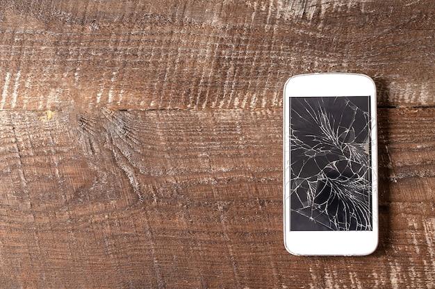 Zepsuty telefon komórkowy z pękniętym wyświetlaczem na brązowym drewnianym tle, leżał płasko.