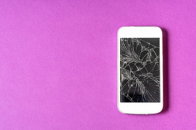 Zepsuty telefon komórkowy z pękniętym wyświetlaczem na fioletowym tle, leżący płasko.
