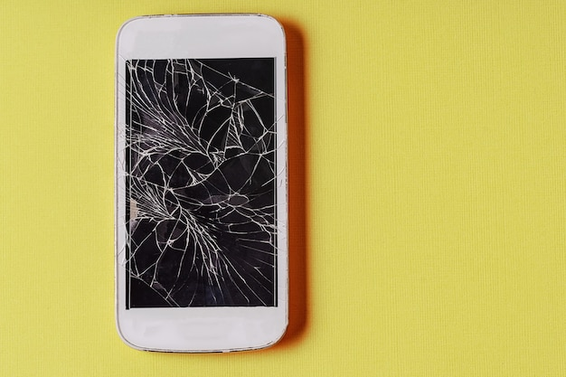 Zepsuty telefon komórkowy z pękniętym wyświetlaczem na żółtym tle, leżał płasko.