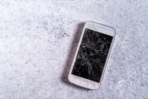 Zepsuty telefon komórkowy z pękniętym wyświetlaczem