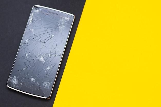 Zepsuty telefon na żółtym i czarnym tle. zgniecione urządzenie z uszkodzonym ekranem reprezentującym wypadek. teksturowany ekran z uszkodzeniem. ciemne szkło ekranu.