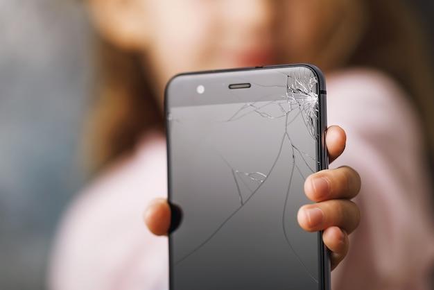 Zepsuty telefon w rękach małego dziecka