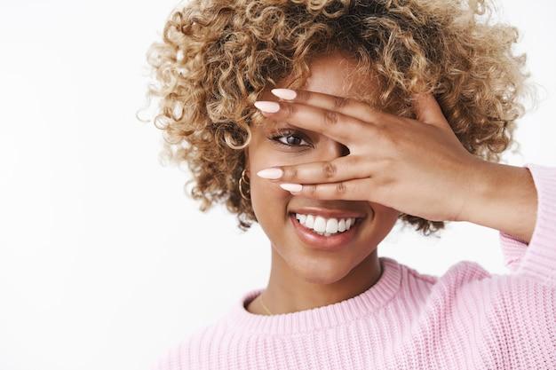 Zerkanie w przyszłość optymistycznym spojrzeniem. portret przystojnej zmysłowej i entuzjastycznej afroamerykanki z kręconymi blond włosami, zamkniętymi oczami i patrzącymi przez palce, uśmiechający się
