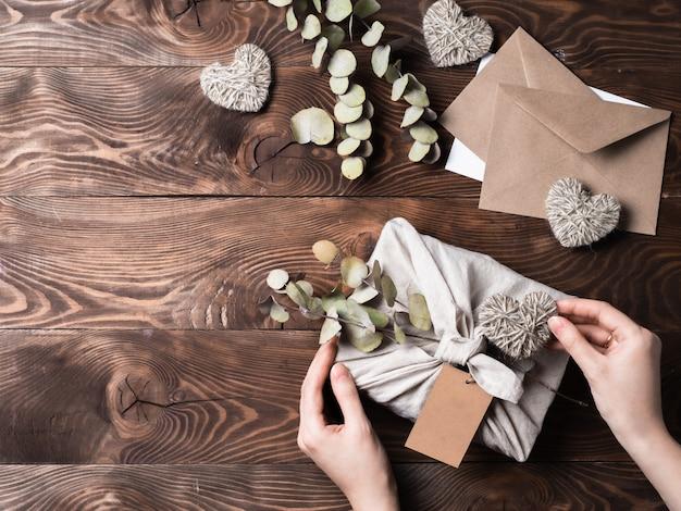 Zero marnotrawstwa walentynki przyjazne dla środowiska opakowanie na prezenty w stylu furoshiki z suchym eukaliptusem. ręce z pudełkiem prezentowym w opakowaniu z tkaniny z pustą etykietą rzemieślniczą na drewnianym tle.