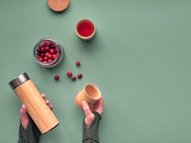 Zero marnowanej herbaty w butelce podróżnej. robienie naparu ziołowego w ekologicznej izolowanej kolbie bambusowej ze smaczną zdrową herbatą żurawinową. nowoczesne mieszkanie leżało, ręce trzymały kolbę i bambusowe kubki, miejsca na tekst.