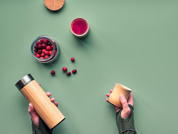 Zero marnowanej herbaty w butelce podróżnej. robienie naparu ziołowego w ekologicznej izolowanej kolbie bambusowej ze świeżą żurawiną. modne mieszkanie leżało. ręce trzyma kolbę i naturalny bambusowy kubek.