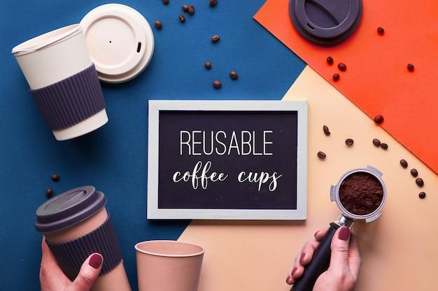 Zero marnowania kawy. ekologiczne kubki do kawy wielokrotnego użytku w rękach, geometryczny widok z góry na podzielonym papierze w klasycznych odcieniach niebieskiego, kremowego i luiawy z lawą z przestrzenią do kopiowania na tablicy.