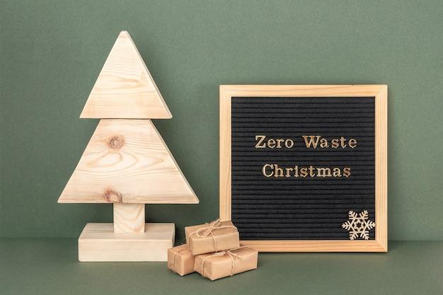 Zero odpadów boże narodzenie tekst na tablicy. domowe drewniane choinki i prezenty na zielonym tle. koncept świąteczny zero waste, ekologiczny. przedni widok.
