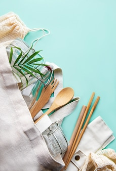 Zero odpadów, brak plastiku i przyjazny dla środowiska styl życia. bawełniana siateczkowa torba, szklana butelka, słoik i bambusowe sztućce na pastelowym zielonym tle. leżał na płasko.