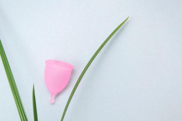 Zero odpadów. koncepcja zdrowia kobiet. przyjazny dla środowiska. różowa menstruacyjna filiżanka na szarego tła zielonej roślinie. alternatywny produkt higieniczny dla kobiet wielokrotnego użytku. styl minimalizmu