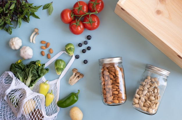 Zero odpadów lifestyle. bawełniana torba netto ze świeżymi warzywami i zrównoważonym szklanym słoikiem na niebieskiej powierzchni płasko ułożona. tworzywo sztuczne do zakupów i dostawy produktów spożywczych.
