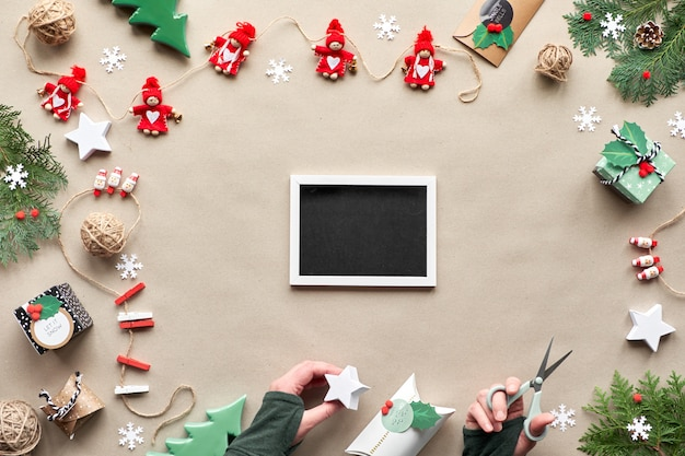 Zero odpadów rama świąteczna z miejscem na kopię. leżał płasko, widok z góry na papierze rzemieślniczym. bibeloty tekstylne, wiecznie zielone, papierowe pudełko w ręku. ekologiczne święta bożego narodzenia. copy-space, miejsce na tekst na tablicy.