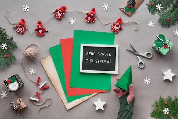 """Zero odpadów świątecznych, leżał płasko, widok z góry na papierze rzemieślniczym z girlandą tekstylną, zapakowane prezenty, czarna tablica z napisem """"zero odpadów świątecznych"""" na papierze. ekologiczne dekoracje świąteczne"""
