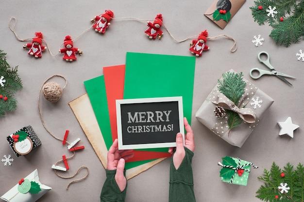 Zero odpadów świątecznych, leżał płasko, widok z góry na papierze rzemieślniczym z tekstylną girlandą lalek, zapakowane prezenty, czarna tablica z tekstem