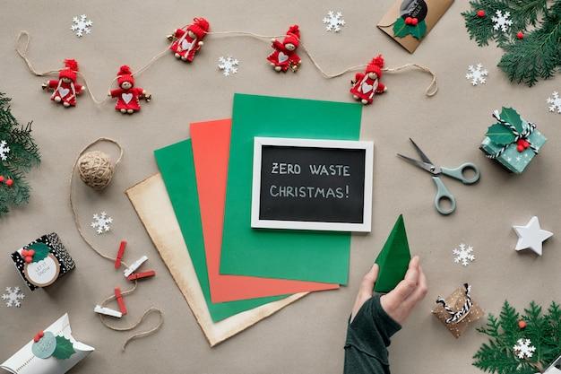 """Zero odpadów świątecznych, leżał płasko, widok z góry na tle papieru rzemieślniczego z girlandą tekstylną, zapakowane prezenty, czarna tablica z tekstem """"wesołych świąt"""" na kolorowym papierze. ekologiczne dekoracje świąteczne."""