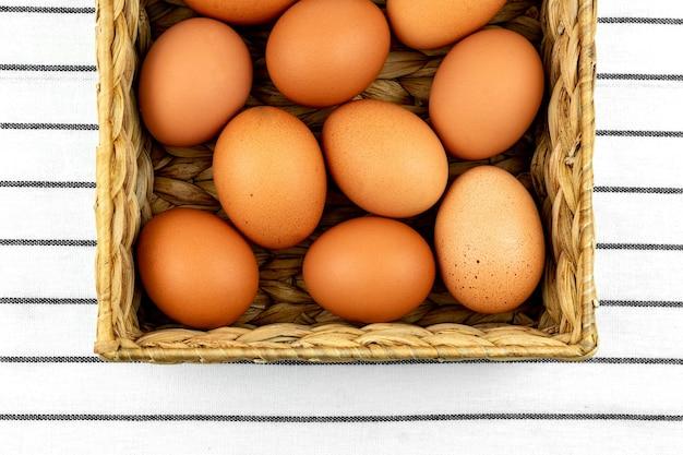 Zero odpadów tło wielkanocne. brak koncepcji plastiku. minimalistyczny styl. beżowe pudełko hiacyntu wodnego z brązowymi kurzymi jajami na tle włókienniczych.