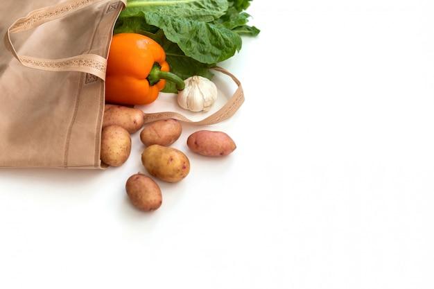 Zero odpadów zużywa mniej plastiku świeże warzywa organiczne w workach z eko-bawełny na drewnianym stole biała torba z płótna z wolnej przestrzeni na zakupy z tworzyw sztucznych