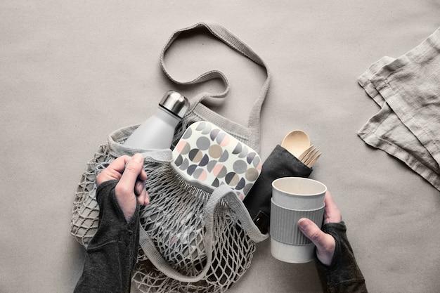 Zero pakowanego zestawu lunchowego, zestaw pudełka na wynos na bawełnianej torbie, organizer bambusowych sztućców, bambusowe pudełko na lunch i kubek wielokrotnego użytku. zrównoważony styl życia, geometryczne płaskie położenie, widok z góry na papierze rzemieślniczym.