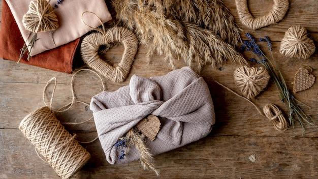 Zero waste koncepcja i makieta na walentynki. tekstylia na opakowanie furoshiki i opakowania prezentowe w stylu furoshiki z lawendą, trawą pampasową i sercami z juty. widok z góry lub układanie na płasko.
