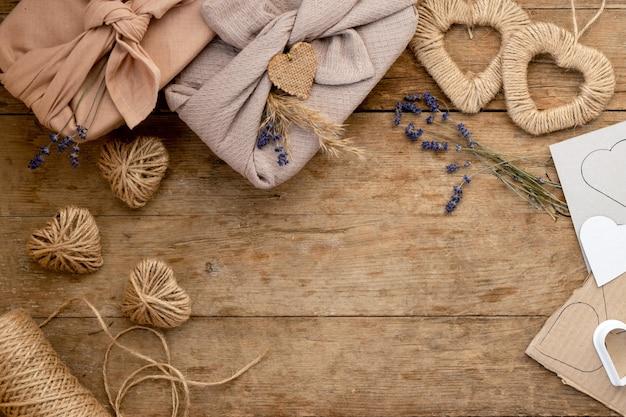 Zero waste koncepcja i makieta na walentynki. zapakowany prezent w stylu furoshiki z lawendą, jutą z trawy pampasowej i wzorowymi sercami. widok z góry lub układanie na płasko.