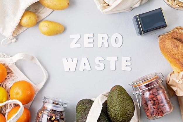 Zero waste zakupy i przechowywanie żywności w bawełnianych torebkach ekologicznych. szklane słoiki z ziarnami, torby wielokrotnego użytku ze świeżymi warzywami, owocami. zrównoważony, etyczny, wolny od plastiku styl życia. widok z góry, płaski układ