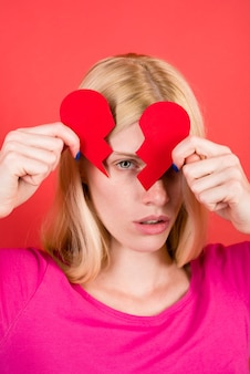Zerwanie relacji smutna kobieta ze złamanym papierowym sercem w rękach nieszczęśliwa miłość czerwona koncepcja miłości