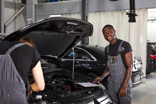 Zespół afrykańskich i kaukaskich mężczyzn pracujących razem w serwisie samochodowym