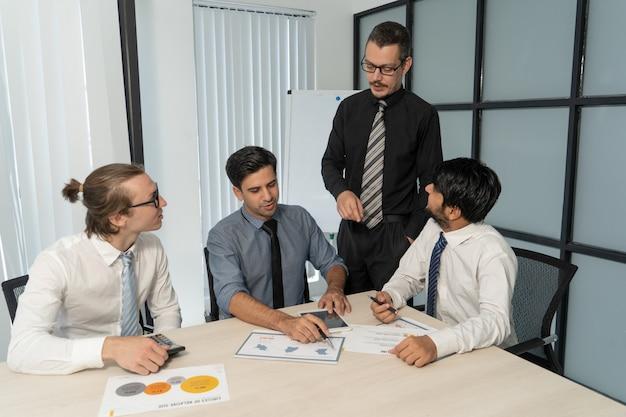 Zespół analityków finansowych pokazujący raport szefowi działu.