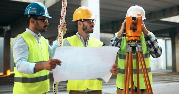 Zespół architektów w grupie na placu budowy sprawdza dokumenty