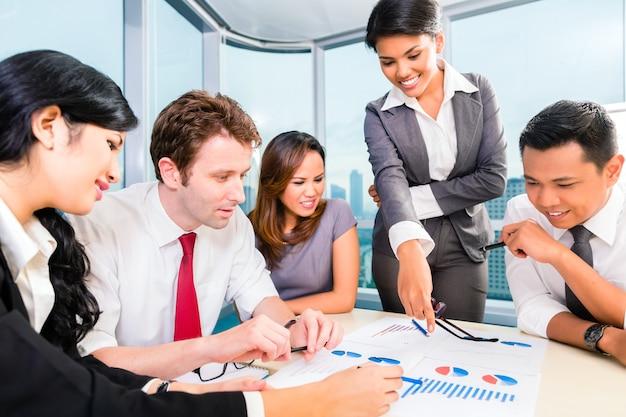 Zespół azjatyckich biznesowych omawianie raportu