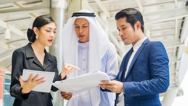 Zespół azjatyckich ludzi biznesu mądry mężczyzna i kobieta rozmawiają i prezentują projekt z plikiem papierowym na świeżym powietrzu dla pieszych w przestrzeni miejskiej nowoczesny budynek