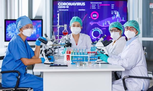 Zespół badaczek skupił się na pracy z mikroskopem i sprzętem laboratoryjnym w laboratorium oraz patrzeniu w kamerę. koncepcja ciężkiej pracy naukowców w epidemii covid-19.