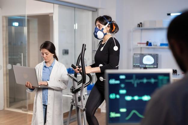 Zespół badaczy medialnych monitorujący vo2 sportów wyczynowych kobiet w masce do biegania. lekarz naukowy w laboratorium mierzący wytrzymałość za pomocą tabletu, podczas gdy skanowanie ekg działa na ekranie komputera w laboratorium.
