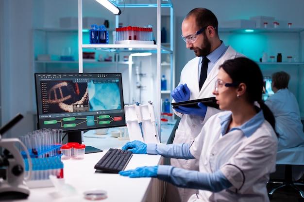 Zespół badaczy pracujących w laboratorium naukowym, biochemia analizująca przykładowe dane na komputerze