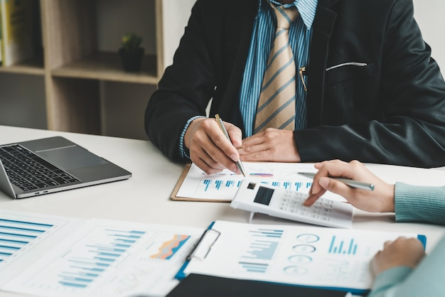 Zespół biznesmena i bizneswoman trzymających pióro za pomocą kalkulatorów, przeprowadzających burzę mózgów, obliczających statystyki, planujących współpracę w biurze. ścieśniać.