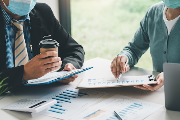 Zespół biznesmenów analizuje statystyczny wykres dochodów za pomocą kalkulatora i wskazuje na wykres, nosząc maskę, aby zapobiec zarazkom w biurze.