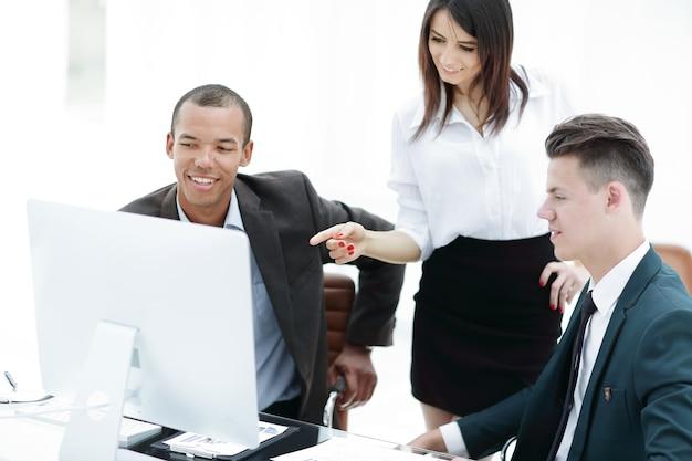 Zespół biznesowy analizujący informacje operacyjne siedzący przy biurku